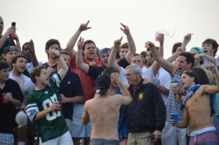 Students and Jerry cheer on the lacrosse team from the hill